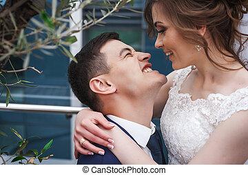 newlywed, összekapcsol dédelget, és, mosolygós, közel, fa, alatt, fényűzés, étterem
