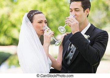 Newlywed couple drinking champagne