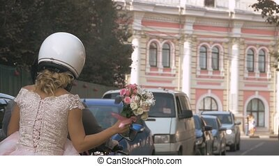 Newlywed couple drive around the city by motorcycle through...