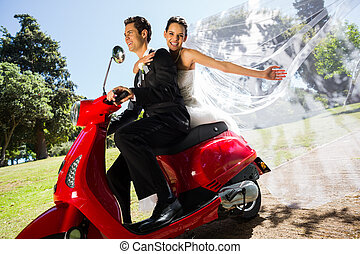 Newlywed couple enjoying scooter ride - Side view portrait...