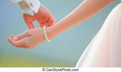 Newlywed couple holding hands. Gentle touch of female and...