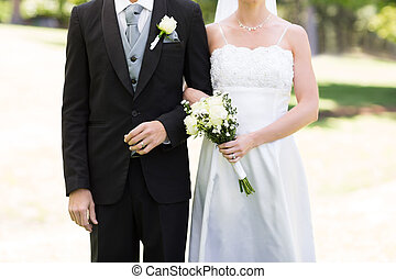 Newlywed couple holding hands in park - Mid section of...
