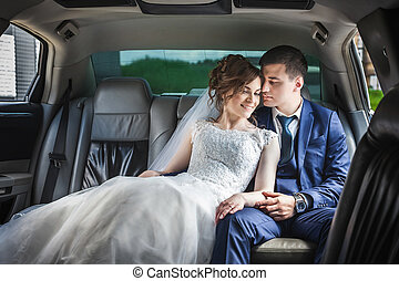newlywed couple hugging in car - portrait of newlywed couple...