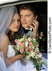 Newlywed couple in wedding car limo