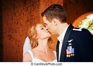 Newlywed Couple Kissing - A newlywed couple enjoy their...