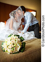 Newlywed couple kissing each other in the bedroom