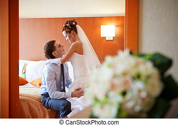 Newlywed couple romancing in the bedroom