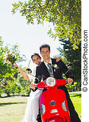 Newlywed couple sitting on scooter in park - Portrait of a...
