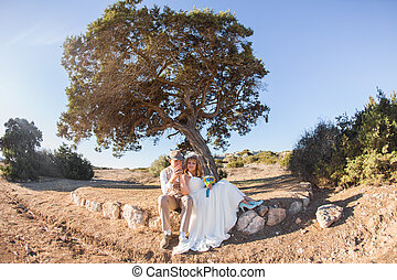 Newlywed couple sitting under a tree in summer