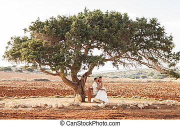 Newlywed couple sitting under shade of tree in summer