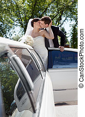 Newlywed Couple Standing Beside Limousine Car Kissing Each...