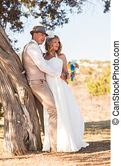 Newlywed couple standing under shade of tree in summer