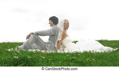 Newlywed pair poses for photographer on grass