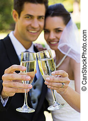 Newlywed toasting champagne flutes at park