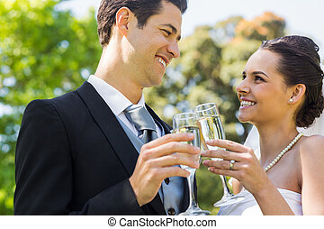 Newlywed toasting champagne flutes at park - Happy young...
