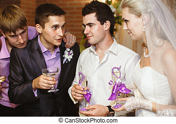 Newlyweds are drinking with their friends on the wedding