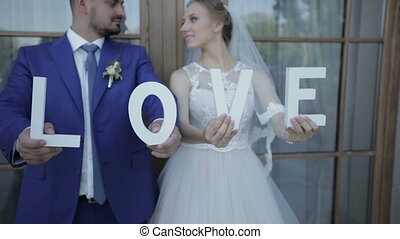 Newlyweds are holding the letter in his hands on a photo shoot