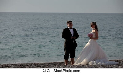 Newlyweds at sea - Young couple standing on the beach.