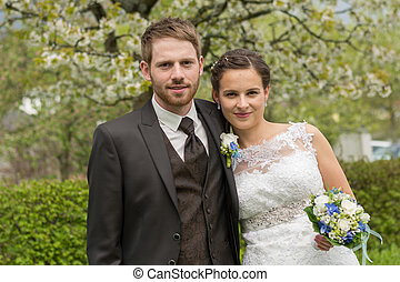 newlyweds before flowering tree