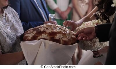 Newlyweds breaking traditional wedding bread at celebration