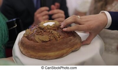 Newlyweds breaking wedding bread unrecognizable