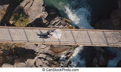 Newlyweds. Bride and groom lie on a bridge over a mountain river. Aerial view
