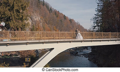 Newlyweds. Bride and groom on a bridge over a mountain river. Aerial view