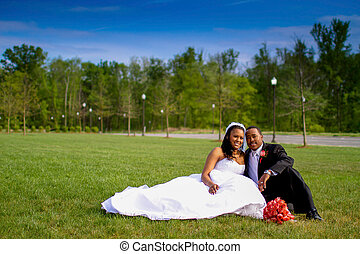 Newlyweds - Bride and groom sitting together in a field near...