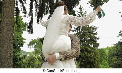 Newlyweds. Caucasian groom with bride dancing in park. ...