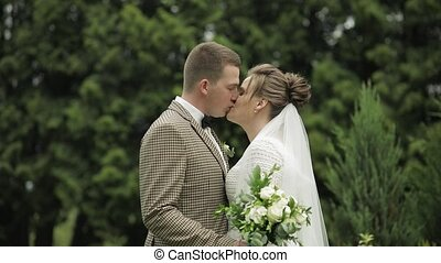 Newlyweds. Caucasian groom with bride kissing in park. ...