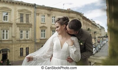 Newlyweds. Caucasian groom with bride kissing on balcony. ...
