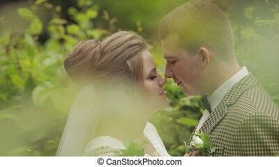 Newlyweds. Caucasian groom with bride making a kiss in park...