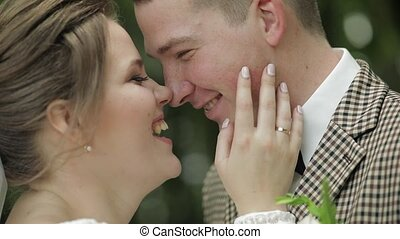 Newlyweds. Caucasian groom with bride smiling in park. ...