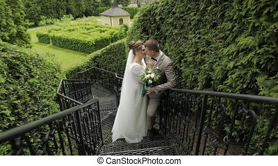 Newlyweds. Caucasian groom with bride stay on stairs in park...