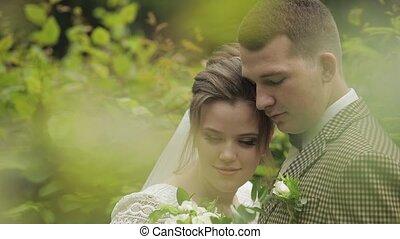 Newlyweds. Caucasian groom with bride walking, embracing, ...