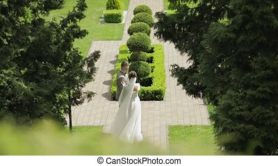 Newlyweds. Caucasian groom with bride walking in park. ...