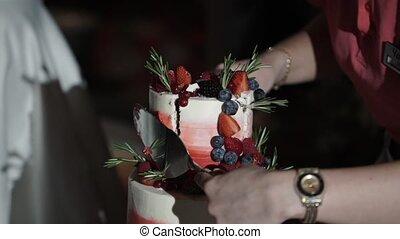 Newlyweds cutting celebration cake at the party indoors