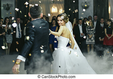 Newlyweds dance in the smoke and rain of confetti