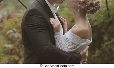 Newlyweds embracing and kissing in the park alley