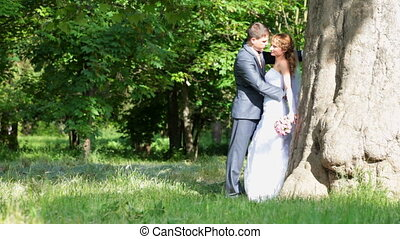 newlyweds embracing - newlyweds are embracing in the park by...