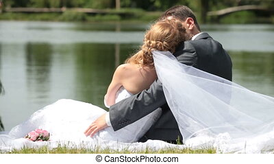 newlyweds embracing each other are sitting on the shore of Lake