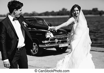 Newlyweds face the wind behind an old car holding each other hands tightly