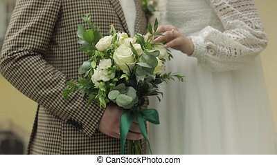Newlyweds. Hands of groom and bride holds wedding bouquet. ...