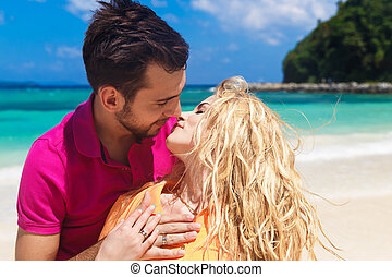 Newlyweds having fun on a tropical beach. Honeymoon
