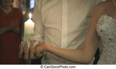 Newlyweds hold burning candle
