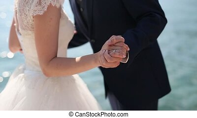 Newlyweds hold hands on the sea. Couple holding hands
