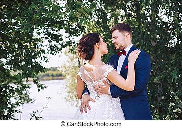 Newlyweds hug on the river bank
