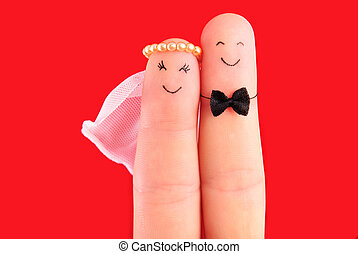just married concept - newlyweds painted at fingers isolated on red background