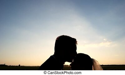 Newlyweds hugging in a wheat field in sunset
