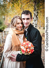 Newlyweds in a coat and scarf on a cold autumn day in the park.